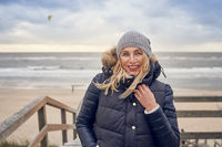 Middle-aged woman braving a cold winter day at the sea