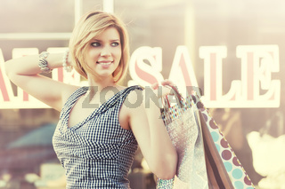 Happy young fashion woman with shopping bags walking in the mall