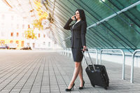 Young beautiful business woman with mobile phone and suitcase in urban setting