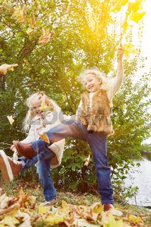 Zwei Kinder spielen und tanzen im Herbst