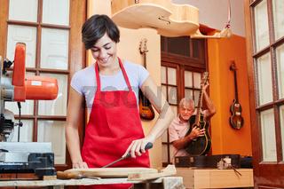 Junge Frau in der Lehre zum Gitarrenbauer