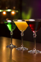 Three exotic cocktails in bar