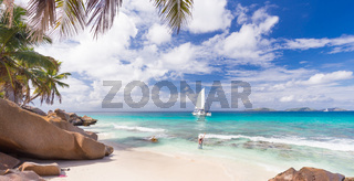 Woman enjoying Anse Patates picture perfect beach on La Digue Island, Seychelles.