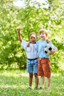 Zwei Jungen mit Fußball als Freunde jubeln