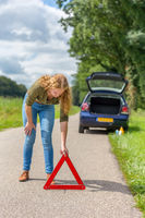 European woman placing hazard warning triangle on road