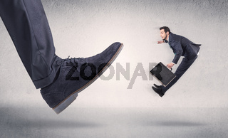 Small businessman kicked by big shoe