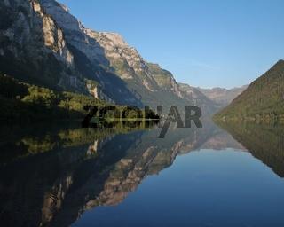 Summer morning at lake Klontalersee, Switzerland. Mountain range mirroring on the surface.
