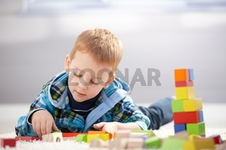 Lovely toddler playing with building cubes at home