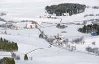 Lovely rural countryside on snowy winter day. Aerial view of barnyards and farm. Weitnau, Allgau, Bavaria, Germany.