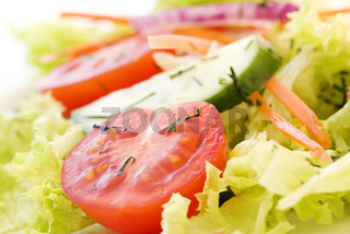 Fresh garden salad with tomato, cucumber and lettuce as closeup
