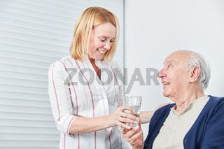 Junge Frau gibt Senior ein Glas Wasser