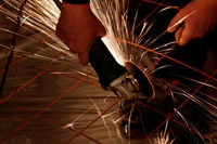 A man working with electric grinder tool on steel structure in factory - sparks flying