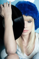 Portrait of  beautiful girl dressed in a blue fur winter hat with  vinyl musical records in her hands