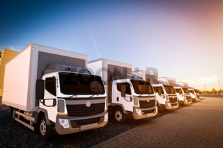 Fleet of commercial delivery trucks on cargo parking