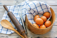 Kitchen utensils and brown eggs in an old sieve.