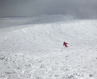 Skier downhill on snowy freeride slope and overcast misty sky before blizzard