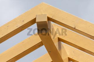 Das Grundgerüst eines Dachstuhls aus Holz, mit Sparren und Firstfette. Ein neues Dach entsteht - auf