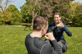 Mann macht Sit-Ups mit Fitnesstrainer