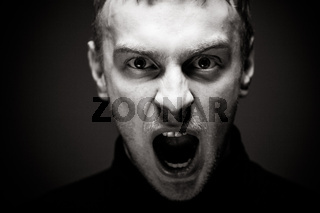 Angry man screaming. A man in a black shirt.