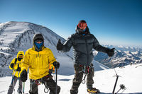A middle-aged climber in a down jacket and harness shows a thumb up next to his friends on the way to the top of a snow-capped mountain