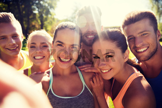 happy friends taking selfie with smartphone