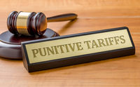 A gavel and a name plate with the engraving Punitive tariff