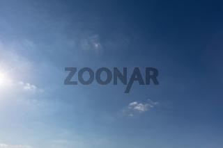Blauer Himmel mit Sonne am Rand und Wolken