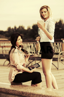 Two young fashion women using tablet computers outdoor