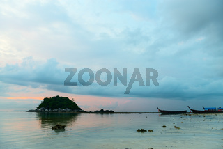 Calm sea at sunset time with islands and boats