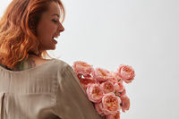 Woman with pink ranunkulus bouquet on a white background
