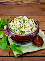Couscous with spinach in bowl on wooden board