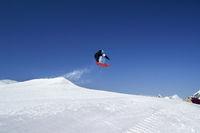 Snowboarder jump in terrain park at ski resort on sunny winter day