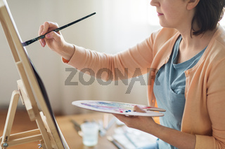 artist with palette and brush painting at studio
