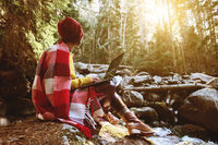 A toned portrait of a freelancer hipster girl with glasses and a stylish cap dressed in a blanket with a laptop kneeling sitting on a rock in a coniferous forest next to a stormy mountain river in warm sunlight