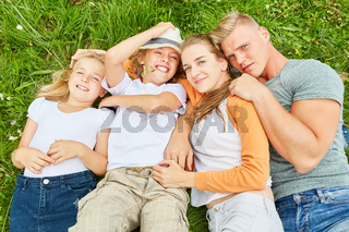 Eltern und Kinder liegen entspannt im Gras