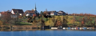 Seegraben, village on the shore of lake Pfaffikon. Colorful trees and fields. Rural autumn scene in Zurich canton, Switzerland.