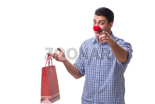 Man with a red nose funny holding a shopping bag gift present is