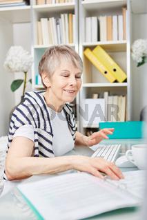 Ältere Business Frau kontrolliert Unterlagen