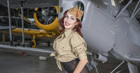 Pin-up, redhead woman dressed as a soldier next to a plane of the second world war, American pinup in the style of the 40s. sensual and sexy woman