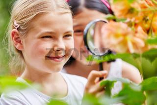 Kinder mit Lupe im Garten
