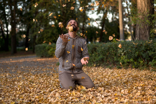 Man in sport wear playing wiht dried leaves in the park.