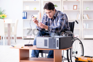 Disabled man on wheelchair repairing computer