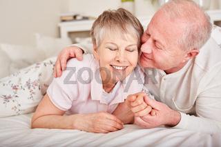 Alter Mann küsst seine Frau