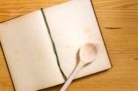 Kochbuch und Kochlöffel auf Holz