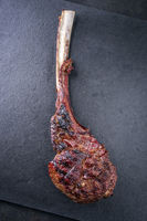 Barbecue dry aged Wagyu Tomahawk Steak as close-up on a slate