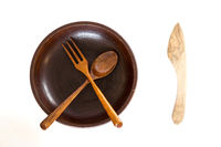 Wooden bowl with knife, spoon and fork on white background