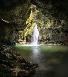 Mystic waterfall in a cave or grotto with green water