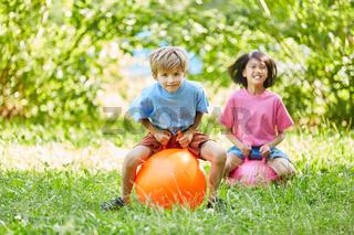 Zwei Kinder hüpfen auf einem Ball