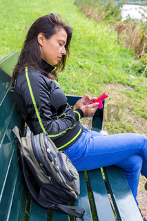 Woman operating mobile phone on  bench in nature