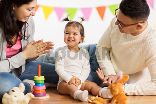 baby girl with parents clapping hands